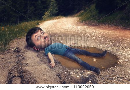 Man with a huge head in the puddle on rut road after rain in forest