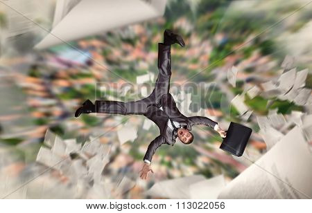 Businessman with suitcase falling from a high building