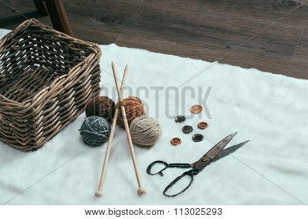 Scissors, Old Basket And Yarn Ball On Carpet