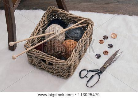 Scissors And Yarn Ball Inside Old Basket On Carpet