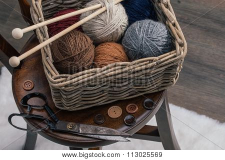 Scissors And Yarn Inside Old Basket On Wooden Chair