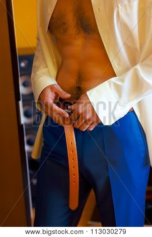 groom getting dressed putting on a belt and wedding pants.