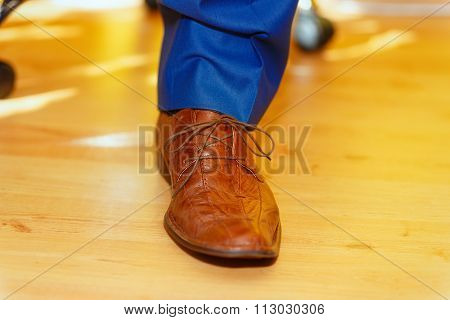 groom brown wedding shoes at home on ocre floor.