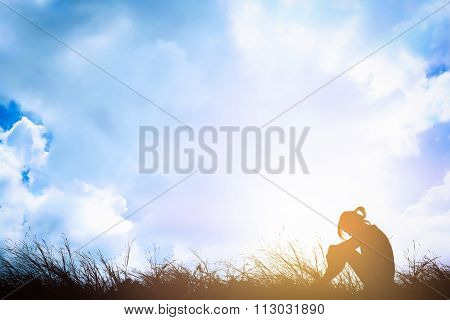 Silhouette Of Sad A Woman Depressed Sitting Alone On Meadow.