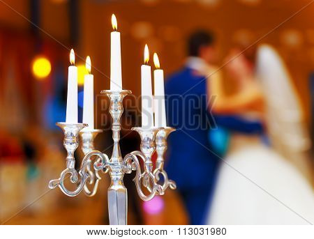 wedding decorative candle holder and dancing bride and groom on background. wedding concept.