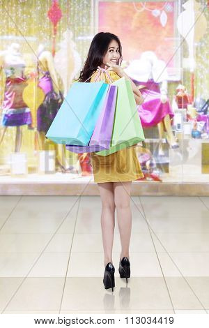 Cheerful Shopaholic Carrying Shopping Bags At Mall
