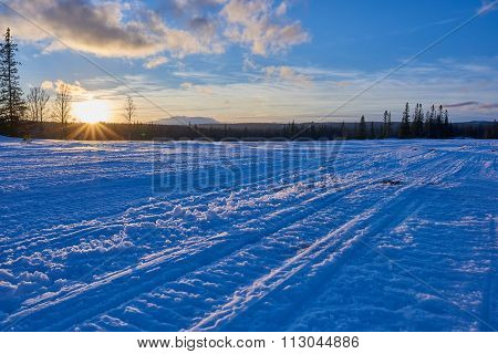 Snowmobile Tracks In Sunset.