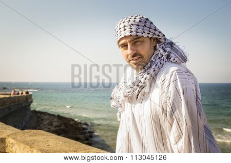 Arab Man Wearing Keffiyeh Seating Near The Beach