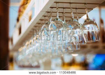 Glasses hanging above bar rack.