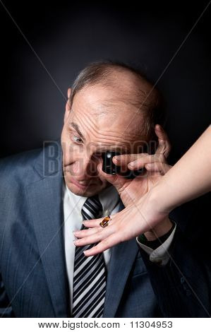 Old Man Appraising Quality Of Ring With Stone