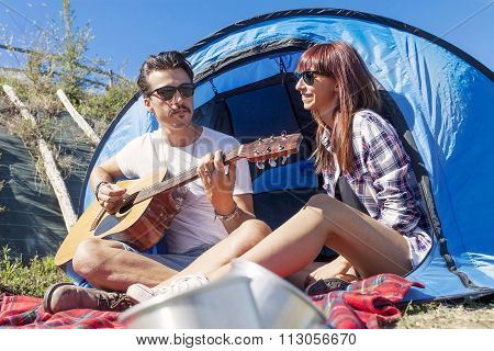 couple of young lovers enjoy playing guitar at the campsite