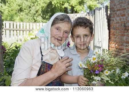 In Summer, The Garden Grandmother With Her Grandson, He Is Holding A Bouquet Of Wildflowers.