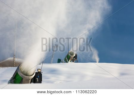 Snow-machine bursting artificial snow  over a skiing slope to alow for the skiing season to start