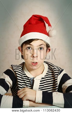 funny close up portrait of a preteen boy in santa hat representing chrisrmas elf with grimace and protruding ears