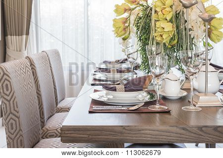 Table Setting On Wooden Dinning Room With Vase Of Flower