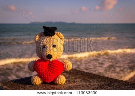 Teddy Bear With Red Heart Sitting Near The Beach - Vintage Tone