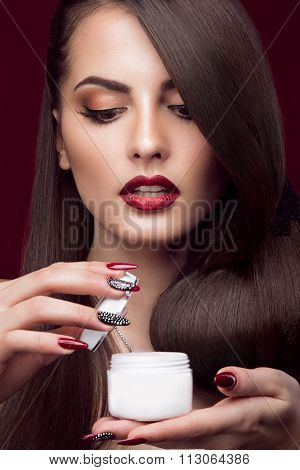 Pretty girl, unusual hairstyle, bright makeup, red lips and manicure design with a jar in her hands.