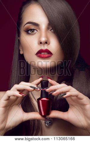 Pretty girl, unusual hairstyle, bright makeup, red lips and manicure design with a jar of nail polis