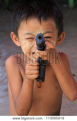 Little boy with toy gun in Myanmar