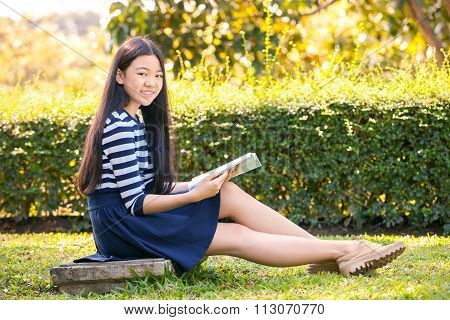 Portrait Of Asian Teen Twelve Years Old And School Book In Hand With Toothy Smiling Face