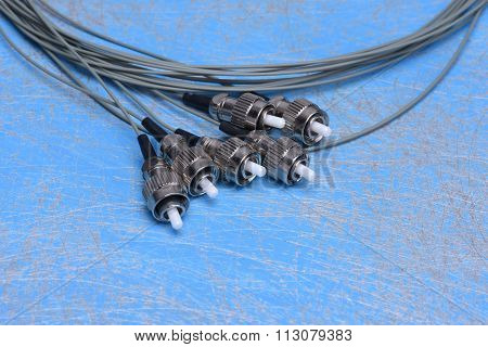 Fiber optic cable pigtails on blue background