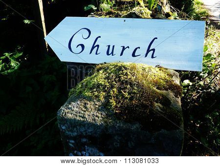 sign pointing in the direction of a church