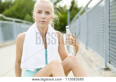 Smiling runner sitting on the ground and takes a break