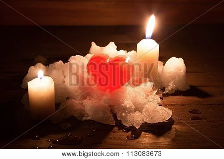 Red Ice Heart And Two Candles On A Hill Of White Snow