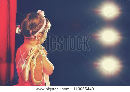 Little Girl Ballerina Ballet Dancer On Stage In Red Side Scenes And Looking In Odeum