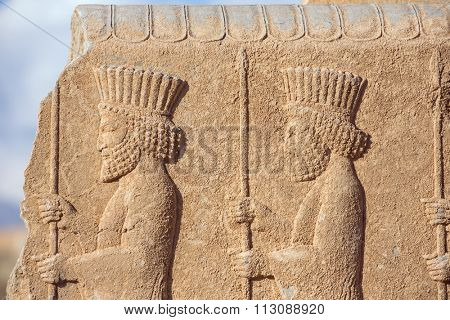 Soldiers of historical empire with weapon in hands. Stone bas-relief in ancient city Persepolis, Iran.