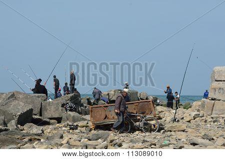 Men fishing off rocks in Sumgait, Azerbaijan