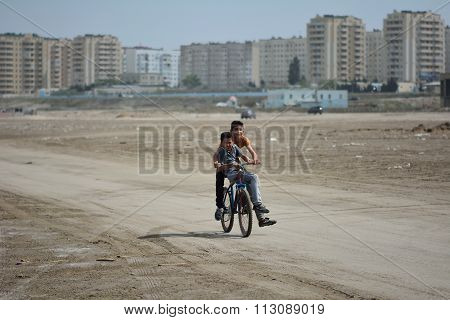 Two boys riding a bike on beach in Sumgait, Azerbaijan