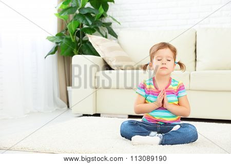 Child Little Girl Meditates In Lotus Position And Practices Yoga