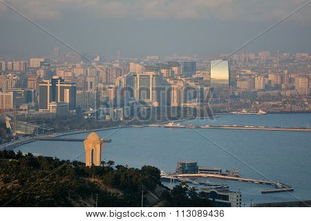View over Baku and the Caspian Sea, in sunshine with haze showing the 20th January monument