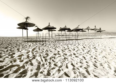 Straw Parasols On Sandy Beach