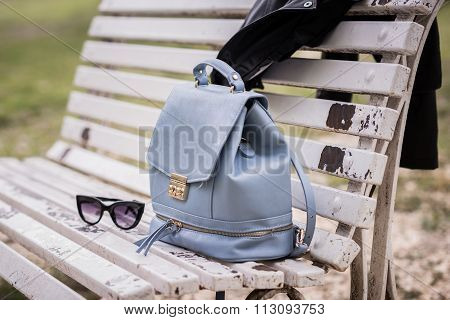 Bag, Sunglasses And Leather Jacket On A Bench