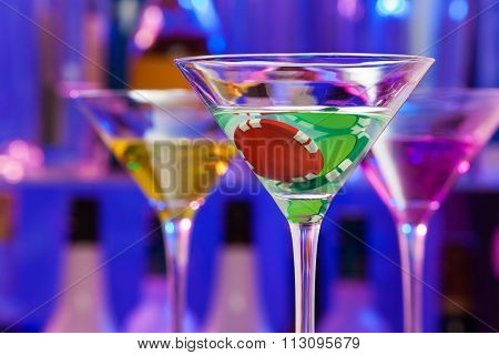 Casino chip in cocktail glasses with bar on back