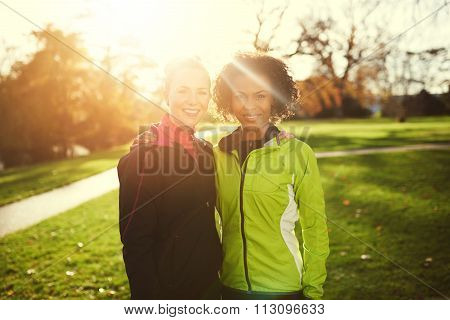 Two Young Female Athletes Hugging While Standing In Park