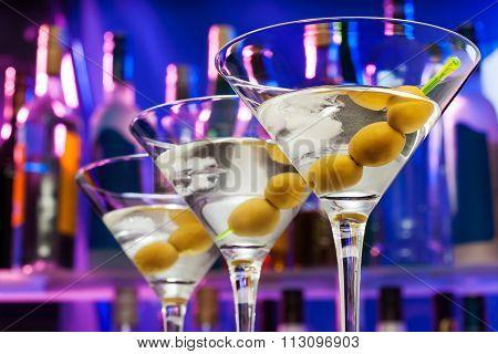Olives in cocktail glasses and bar bottles