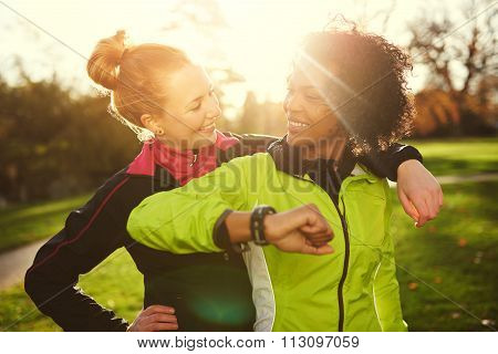 Two Girlfriends In Sportswear Looking At Each Other While Hugging