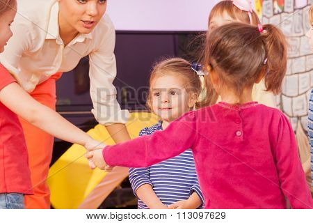 Little girl in circle of friends and teacher