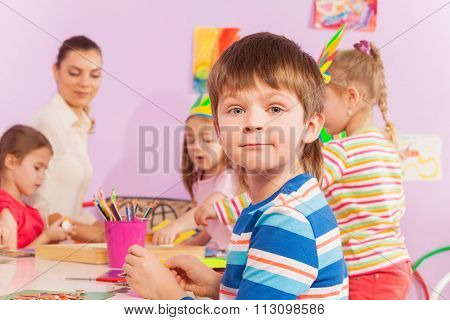 Boy by the table in kindergarten class with mates