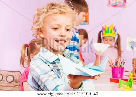 Blond handsome boy shows origami