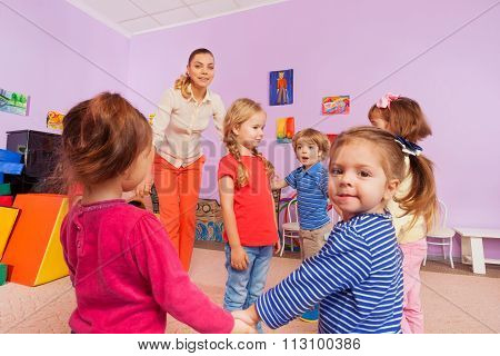 Group of children roundelay around little girl