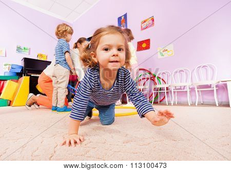 Girl crawl on active class lesson in kindergarten