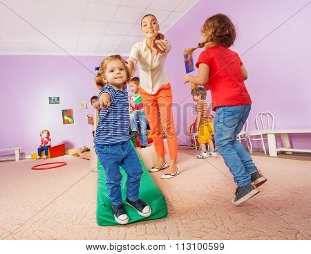 Teacher points running and jumping kids to viewer
