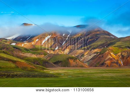 National Park Landmannalaugar, Iceland. Pink dawn in the Arctic. Striped mountains of rhyolite covered sunrise