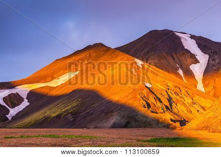Sunrise National Park Landmannalaugar, Iceland. Fairy dawn. Valleys, mountains and glaciers covered with warm orange light