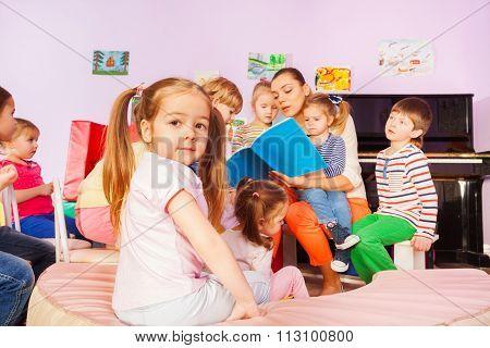 Group of kids listen to teacher reading book