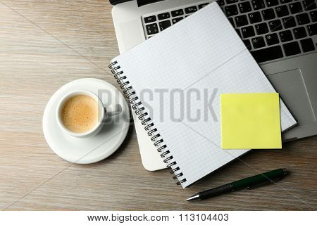 Empty yellow adhesive paper, notebook on laptop keyboard, pen and coffee cup on desk background